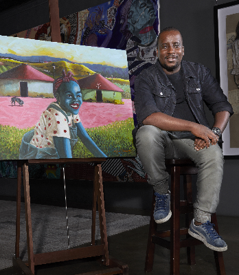 Danca poses alongside one of his most recognisable pieces 'Gentle Days in Africa'